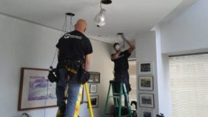 on ladders to install light fixtures